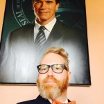 Image of Dr. Cressey in front of the official portrait of Gov Schwartzenegger